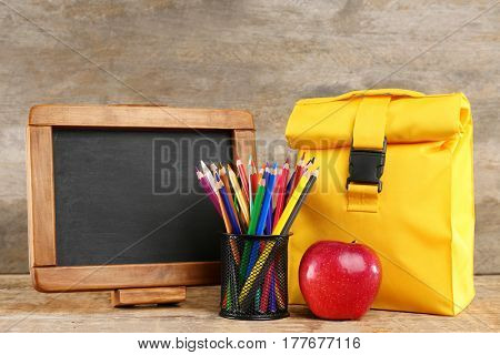 Lunch bag, holder with pencils and small blackboard on wooden background