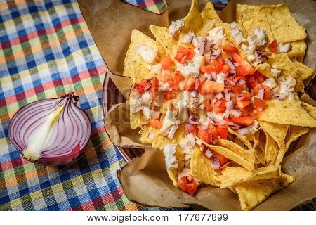 From above shot of crispy nachos served with tomatoes and red onion.