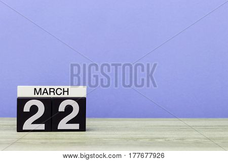 March 22nd. Day 22 of month, calendar on table with purple background. Spring time, empty space for text.