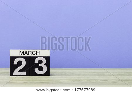 March 23rd. Day 23 of month, calendar on table with purple background. Spring time, empty space for text.