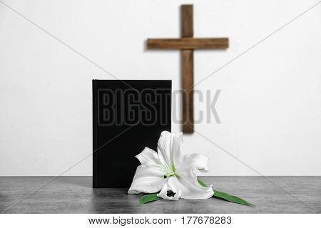 Composition with Bible, lily and cross on light background