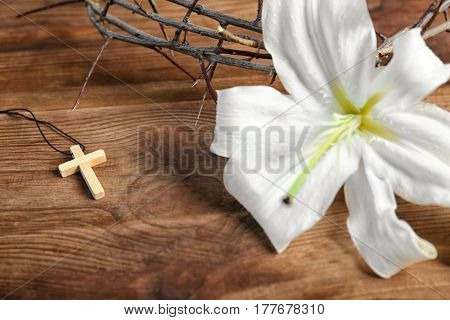 Composition with cross, lily and crown of thorns on wooden background