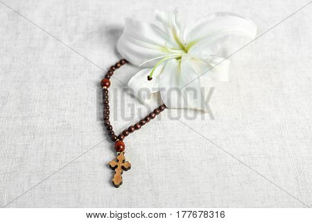 White lily and rosary on light fabric background