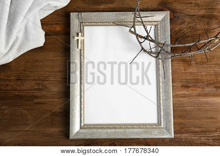 Photo frame, crown of thorns and cross on wooden background