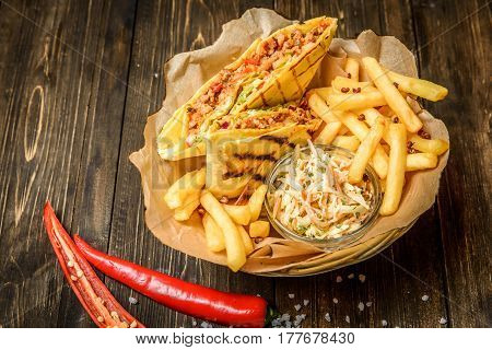 Straw bowl with grilled burritos served with fries and cole slaw.