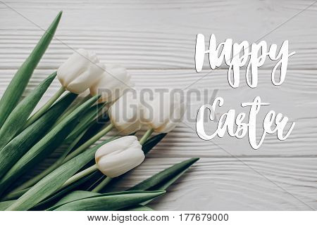 Happy Easter Text Greeting Card Sign On Stylish White Tulips On Rustic Wooden Table Background Top V