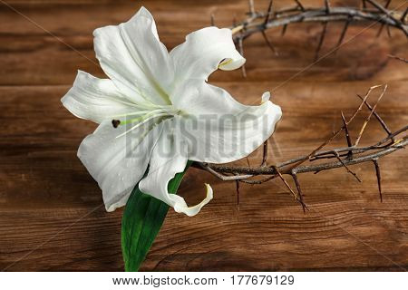Composition with crown of thorns and white lily on wooden background