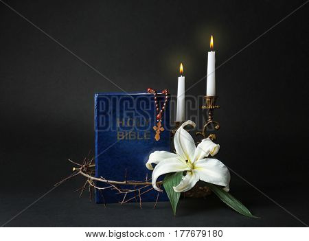 Holy Bible, crown of thorns and Easter white lily on dark background