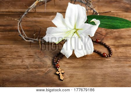 Composition with rosary, lily and crown of thorns on wooden background