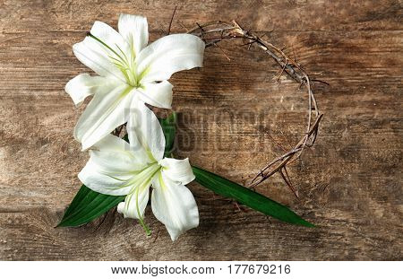 Crown of thorns and Easter white lily on wooden background