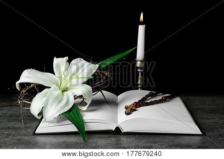 Holy Bible, rosary and Easter white lily on dark background
