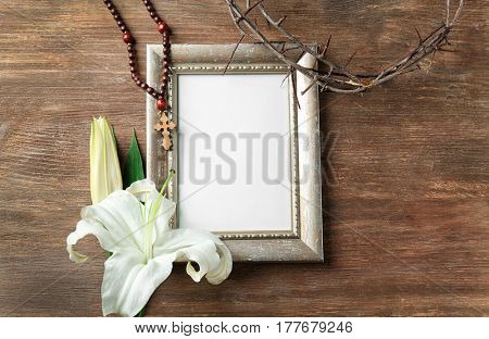 Frame, crown of thorns and Easter white lily on wooden background