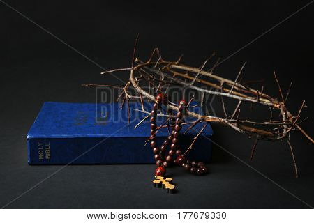 Holy Bible, crown of thorns and rosary on dark background