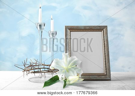 Composition with crown of thorns, lily, photo frame and candlesticks on light background