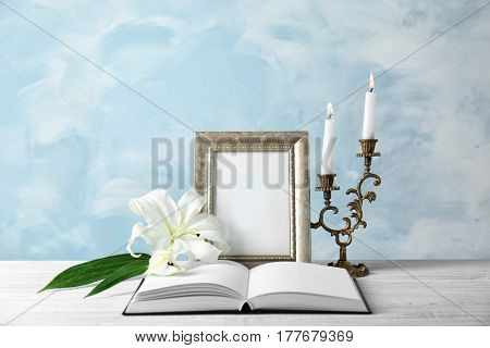Composition with photo frame, candles, opened book and lily on light background