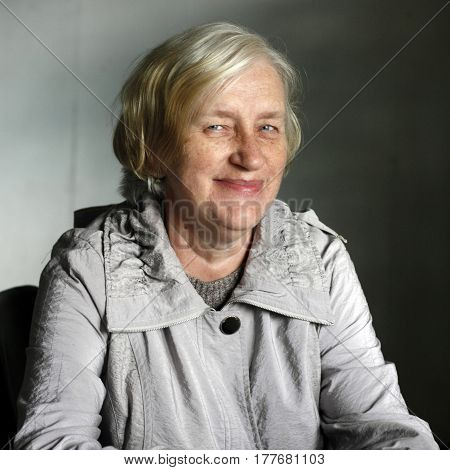 Elderly woman with blonde hair and freckles smile face dressed in a raincoat and a wool sweater