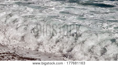 large sea waves with white foam on the choppy blue sea