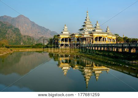 Kyaut Ka Lat Buddhist Temple reflecting in the water of the lake at sunset. Hpa-An Myanmar.