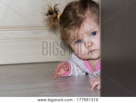 A small child peeks out from behind the wardrobe. The girl with long hair braided in pigtails.