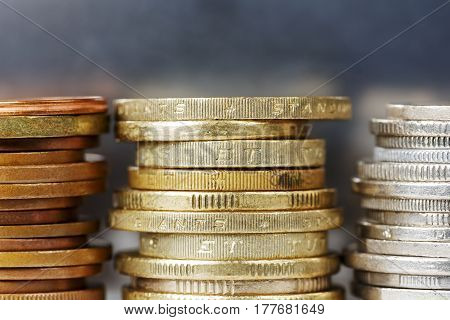 Coins in golden and silver colors stacked against dark silver background