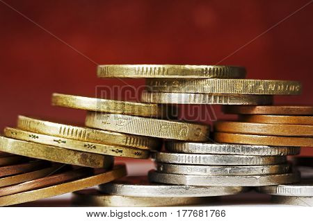 Coins stacked in a chaotic manner against dark background