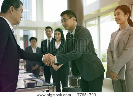 Business people greeting by handshake and take a bow