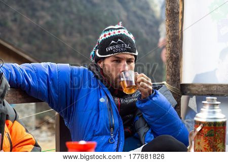 Member of Ukrainian expedition to Mera Peak in warm down Jacket and woollen Hat with Everest Base Camp sign drinks Tea. Kothey Lodge, Nepal, Solo-Khumbu region, November 2, 2016