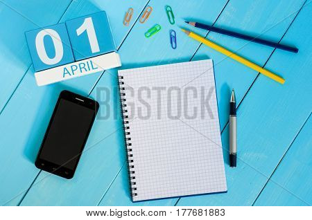 April 1st. Image of april 1 wooden color calendar on blue background. Empty space for text. All Fool's Day.