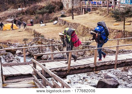 Porters of Himalaya Mountain expedition carrying heavy bags walking crossing wooden bridge. Kothey Lodge, Nepal, Solo-Khumbu region, November 2, 2016