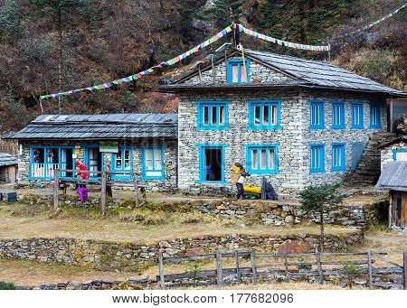Stone Building at remote Lodge in Himalaya Mountains decorated by traditional buddhist prayer flags. Kothey Lodge, Nepal, Solo-Khumbu region, November 2, 2016