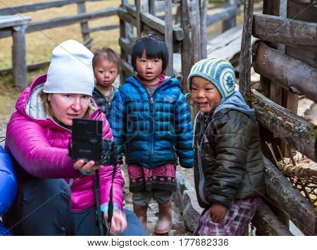 Western Woman taking Photo of little Nepalese Children in remote Himalaya Village expressing diverse emotions. Kothey Lodge, Nepal, Solo-Khumbu region, November 2, 2016