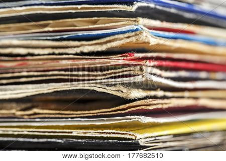 Stack of old vinyl records that are in colorful covers