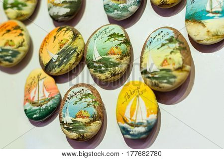 Palanga Lithuania - August 9 2012: Souvenir decorative pebbles with image of Palanga views hut on shore of sandy beach and sailboat on waves in sea. Tourist Souvenirs for memorable shopping