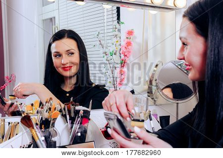 hands of make up artist. Many cosmetics and brushes on a table in salon. Work in beauty salon. cosmetics on wooden workplace. Eye shadow blush powder professional cosmetics and makeup brushes.