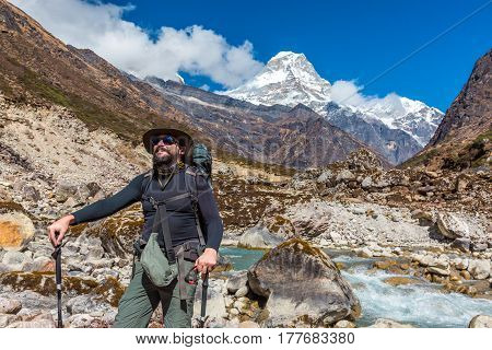 Mature sportive Traveler in Fedora Hat with Backpack and walking Poles staying on Footpath and looking up