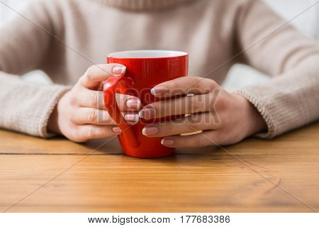 Close-up of woman holding cup of tea while sitting at wooden table in cozy coffee shop, shallow depth of field. Girl enjoying mug with hot drink at urban cafe and warming hands