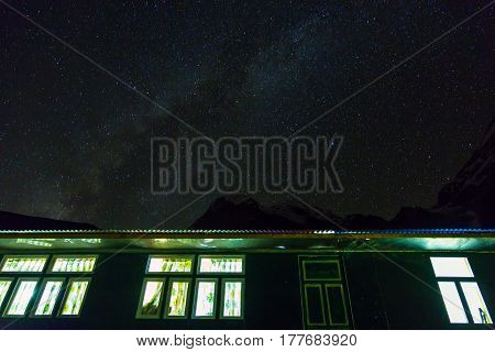 View of Mountain Lodge with illuminated Windows and Night starry Sky on Background