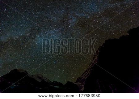 High Altitude Mountain Ridge with sharp rocky and snowy ridges and peaks at night sky with many stars and milky way on background