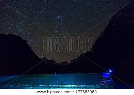 View of Mountain Lodge Roof with Night starry Sky on Background. Traditional Nepalese Stone Building and Slate Loft with Satellite antenna