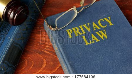 Book with title Privacy Law on a wooden surface.