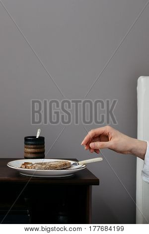 Female in Bed Reaching for Toast on Bedside Cabinet
