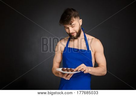 Hot sexy naked handsome man with chocolates, chocolate candies. Smiling naked handsome man wearing dark blue apron holding a white plate with many sweets, chocolate candies. Handsome confectioner.