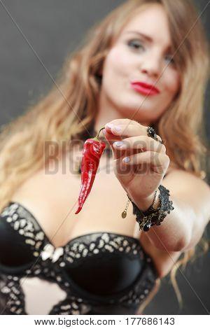 Sensual seductive attractive woman wearing lingerie holding chilli pepper. Erotic fashion concept