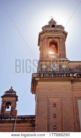 Bottom view of the two towers of the church with a bell and a clock on the blue sky background