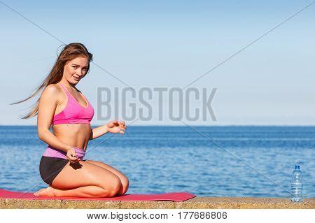 Woman In Sportswear Sitting On Dyke By Sea