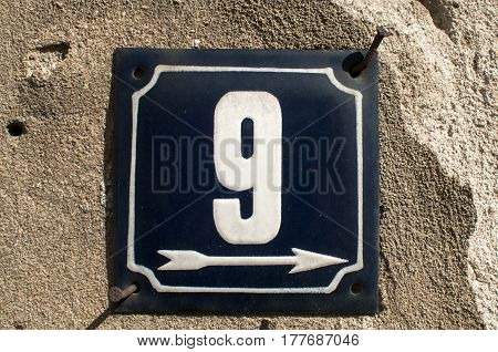Weathered grunge square metal enameled plate of number of street address with number 9 closeup