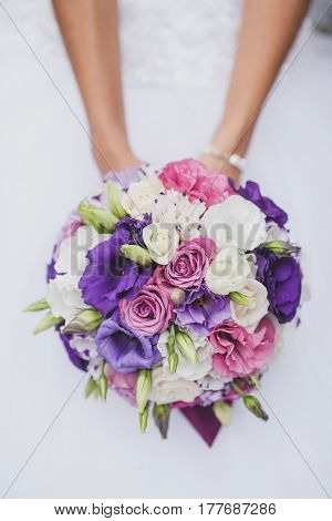 Bride in a white wedding dress holding a flowers bouquet from purple rose in hands. Wedding bridal bouquet on a white background close up. wedding flowers concept.