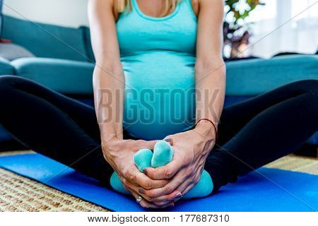 Young Pregnant Woman Doing Yoga At Home