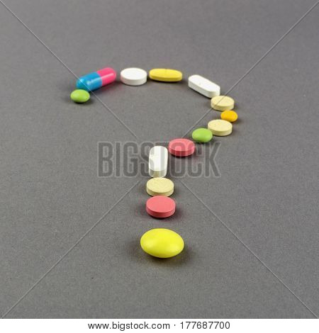 Question mark created from colored pills. Medical concept.