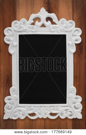 White Ceramic Frame With Stucco Molding, Black Empty Space On Dark Wooden Background.